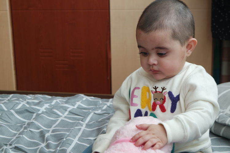 Cute baby boy on bed at home