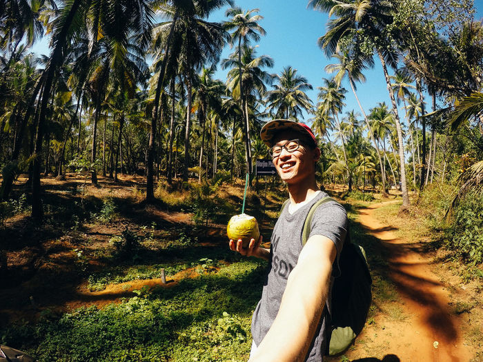 Smiling young man holding coconut water on field during sunny day