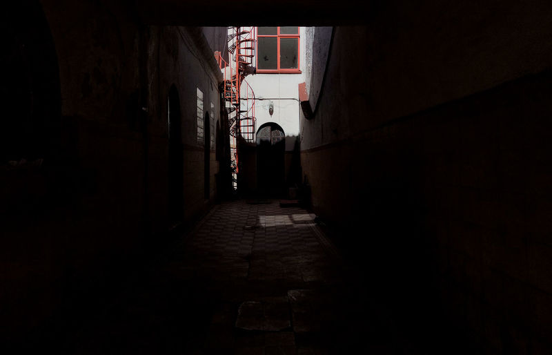 Narrow alley amidst buildings at night