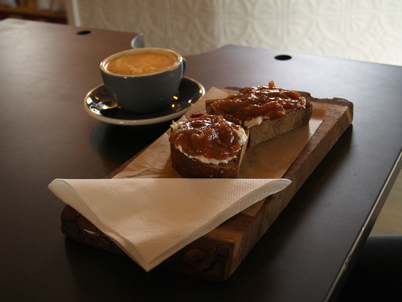 Bread Served On Cutting Board By Coffee Cup On Table