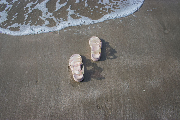 High angle view of man lying down on wet sand