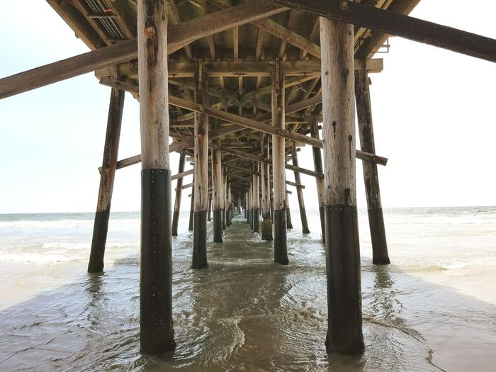 Low Angle View Of Wooden Pier On Sea