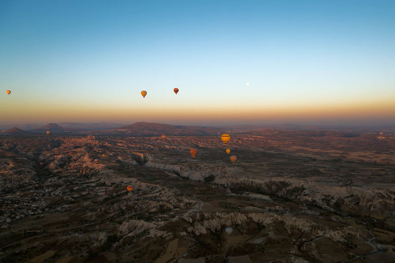Hot air balloons flying over cappadocia against clear sky during sunset