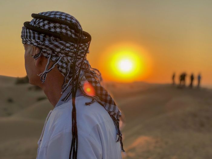 Side view of man standing at desert during sunset