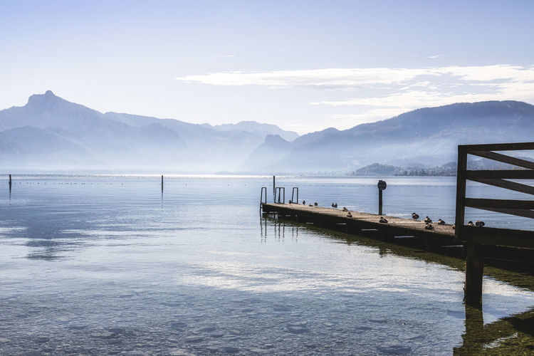 Pier on lake by snowcapped mountains against sky