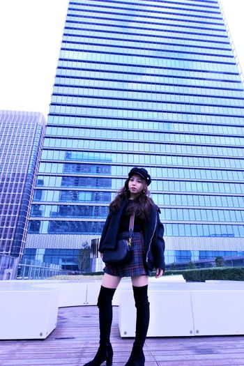 Portrait of young woman standing against modern building