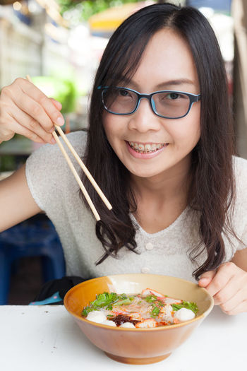 Close-up portrait of smiling young woman eating food