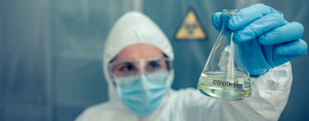 Close-up of scientist holding liquid in flask