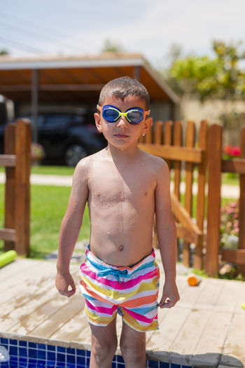 Portrait of shirtless boy standing in swimming pool