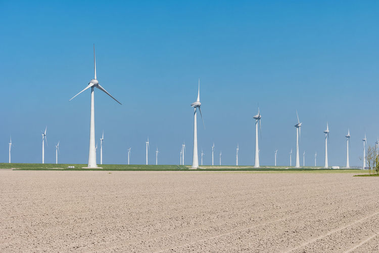 Windmill on field against blue sky, windmills by sea against sky, windmills park westermeerdijk