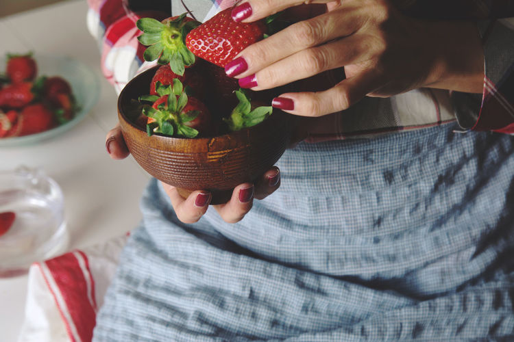 bowl of strawberries in the hands of a woman with apron, sitting at the table Red Sitting Woman Bowl Container Delicious Die Food Food And Drink Freshness Fruit Holding Human Body Part Human Hand Indoors  Indoors  Lifestyles One Person Organic Real People Seasonal Strawberry Women