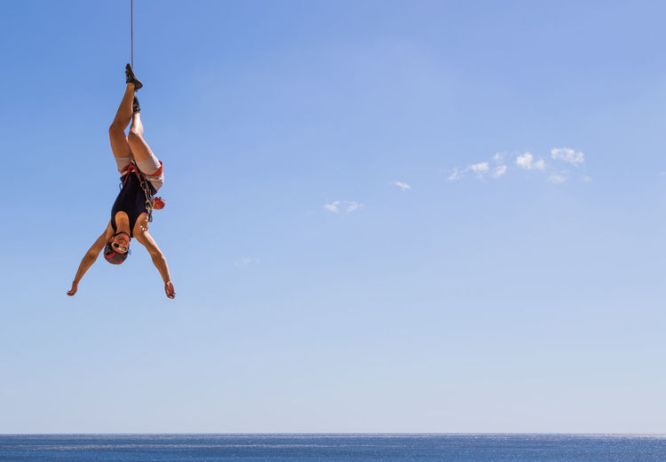 Woman Hanging Over Sea Against Sky