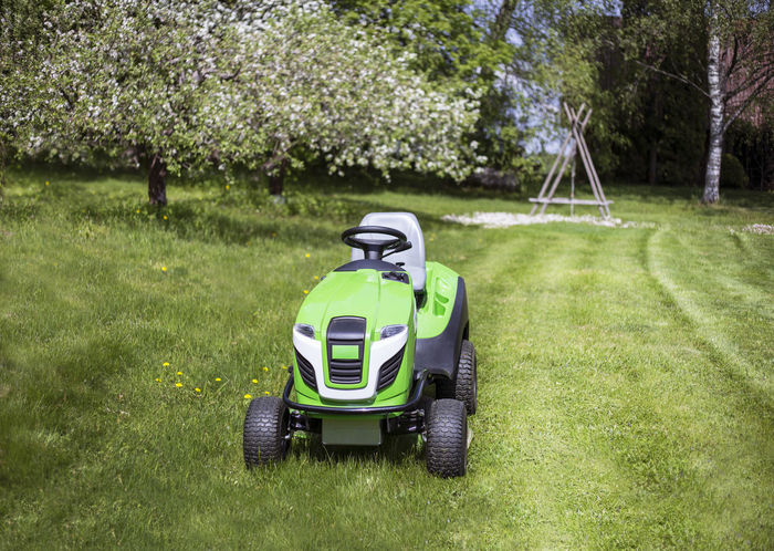 Riding mower, mowing grass in yard, tractor. Apple tree, bloom, garden. Apple Tree Backyard Blooming Countryside Cutter Gardening Grass Grass Cutter Grass Cutting. Green Color Home Homestead Lawn Cutter Lawnmower Mowing Mowing The Lawn Mowing Tractor Nature No People Riding Mower Spring Tractor Transportation Tree Yard