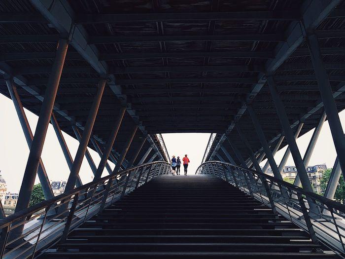 Rear view of people on footbridge
