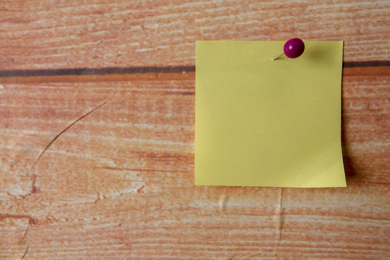 YELLOW STICKER STICK ON A WOODEN BACKGROUND Adhesive Note Blank Brown Close-up Copy Space Indoors  No People Note Office Paper Red Reminder Single Object Still Life Table Thumbtack Trapped Two Objects Wood - Material Wood Grain Yellow