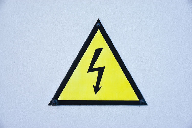 Warning symbol. High voltage sign. Yellow Triangle Shape Sign Shape Pattern Black Color Safety Geometric Shape Warning Symbol Copy Space Arrow Symbol Electricity  Warning Sign Communication High Voltage Sign Indoors  Photography Travel Beautiful Backgrounds Danger Zone White Background Zoom Ideas
