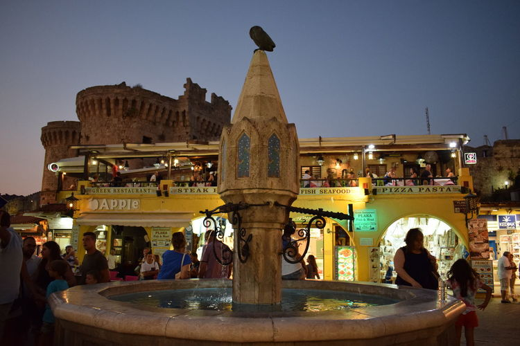 Evening Lights Fountain Rhodes Rhodes Old Town, Greece Ródos Architecture Building Exterior Built Structure Clear Sky Evening Evening Sky Illuminated Leisure Activity Lifestyles Outdoors Owl People Real People Sculpture Water