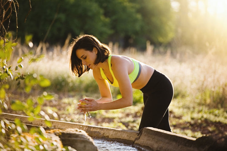 Young sporty woman washing an apple in the field at sunset after running Sporty Woman Sporty Girl Young Woman Crop Top Sportswear Field Runner Yoga Healty Fitness Attractive Sunset Sport Clothes Spring Summer Brunette Leggings Crop Tank Outdoors Lifestyles Exercising Recreational Pursuit Energy Nature Caucasian Athlete