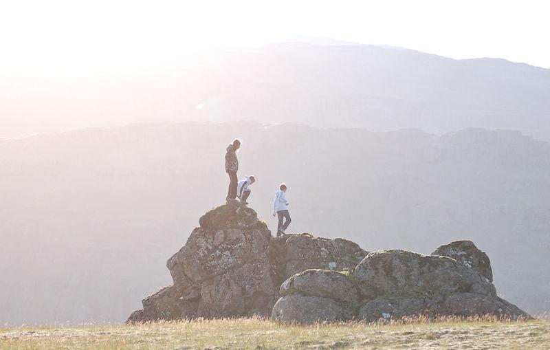 Friends Walking On Rock Against Mountain