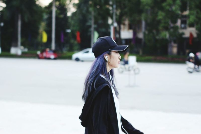 Side view of young woman wearing cap walking in city