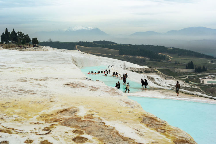 A view across Pamukkale's travertine terraces and the bathing pools with tourists a cluster of trees with snow capped mountains in the background. Pamukkale, Turkey. Turkey Beauty In Nature Crowd Day Group Of People Holiday Hot Spring Land Large Group Of People Leisure Activity Lifestyles Men Mountain Nature Outdoors Pamukkale Real People Sky Trip Vacations Water Women