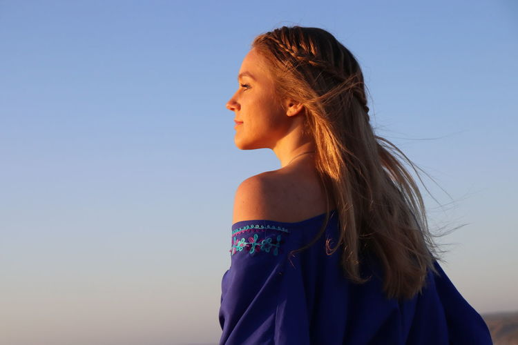 Portrait of woman looking away against clear blue sky