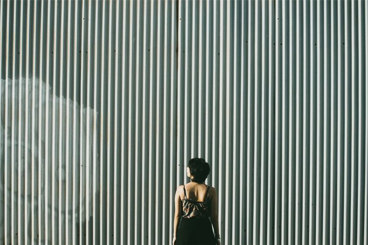 Rear view of woman standing on metal wall