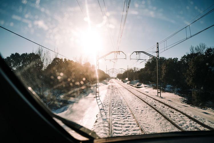 Railroad tracks against sky seen through glass