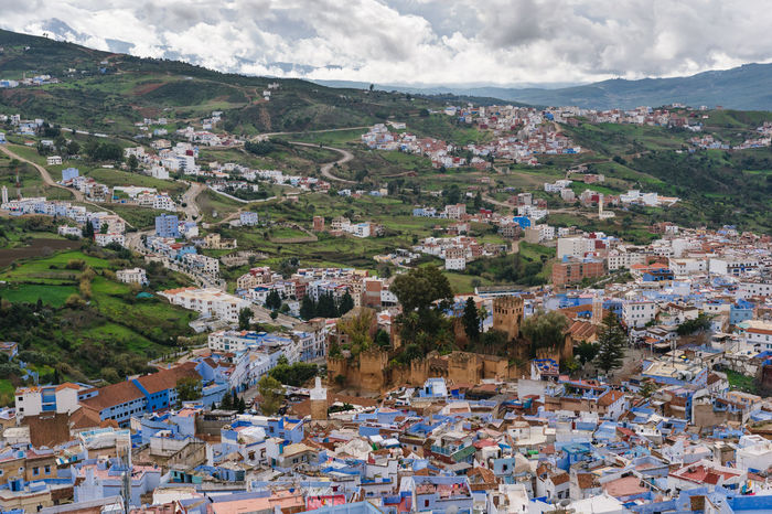An awesome panoramic view over the blue painted and famous city Chefchaouen in Morocco. It is located in the Rif Mountains. The sky is cloudy. Africa Architecture Background Berber  Blue Building Exterior Chaouen Chefchaouen City Cityscape Culture Medina Morocco Mountain Nature Old Panorama Panoramic Rif Rif Mountains Sky Street Town Travel View