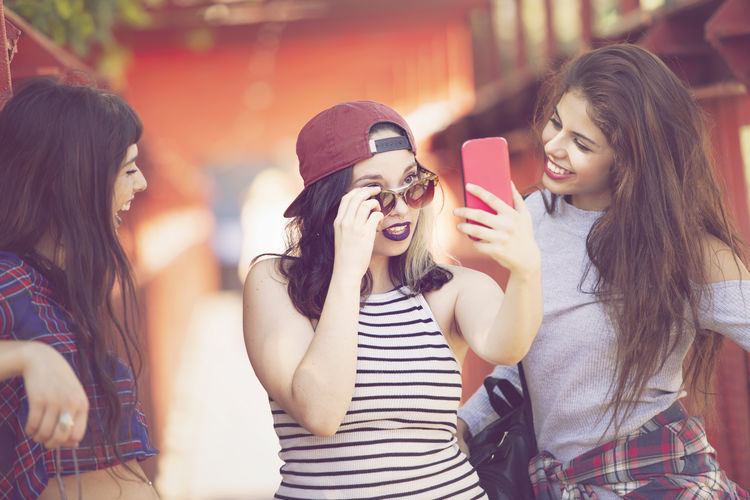 Smiling Young Woman Taking Selfie With Friends