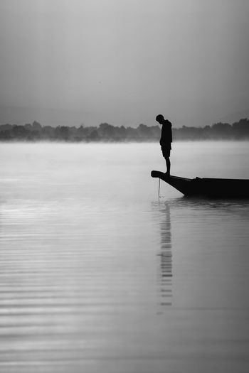 Side view of silhouette man on lake against sky