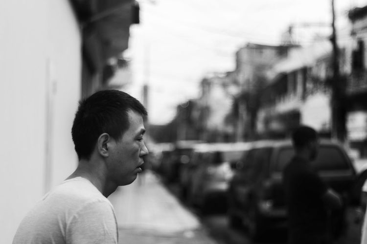 Portrait of man looking at city street