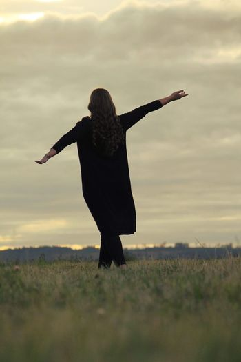 Surface level view of woman with arms outstretched on grassy field