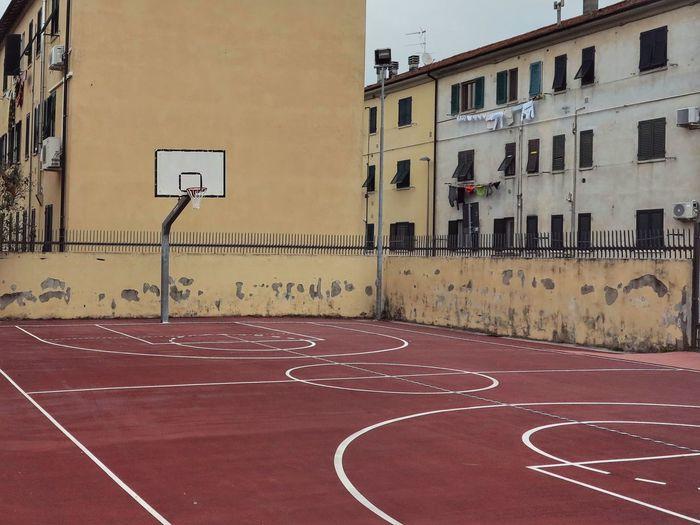 Basketball hoop by buildings in city