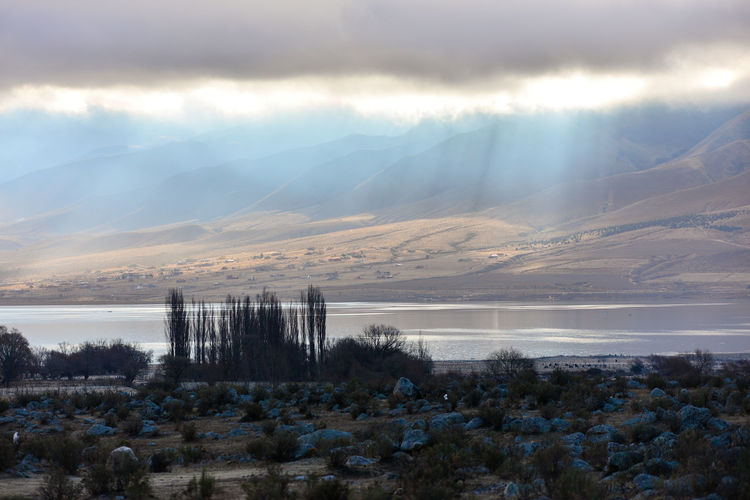 Sunlight Streaming Through Clouds On River And Mountains