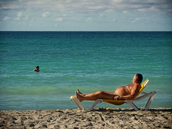 Side view of shirtless man relaxing on deck chair at beach against sky