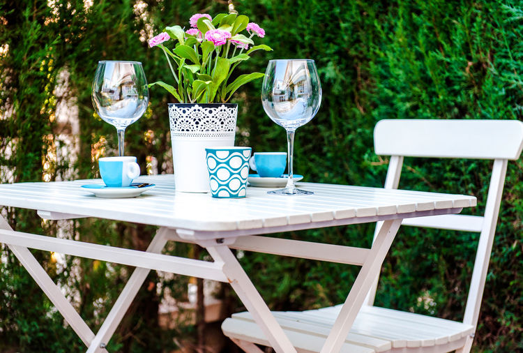 Wineglasses with cups and flower pot on white table in yard