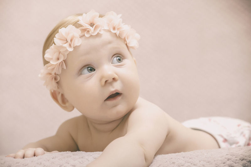 Close-up of cute baby girl wearing tiara lying on bed