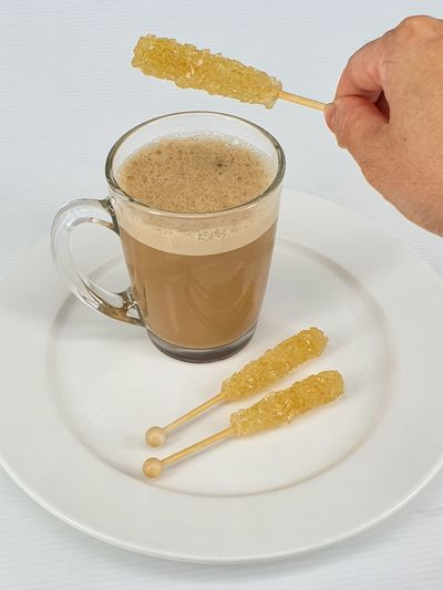 High angle view of hand holding coffee served on table