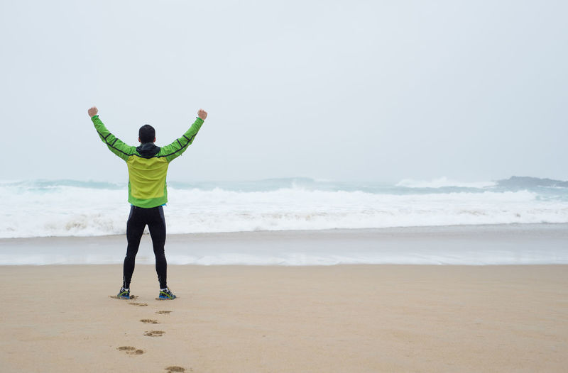 Rear view of man with arms raised standing at beach