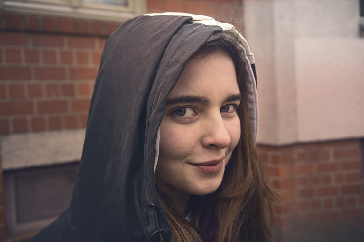 Woman Smile Hood Outdoors Portrait Headshot One Person Young Adult Looking At Camera Real People Brick Brick Wall Lifestyles Hair Young Women Focus On Foreground Hairstyle Leisure Activity Hood - Clothing Long Hair Front View Wall Beautiful Woman Contemplation Teenager