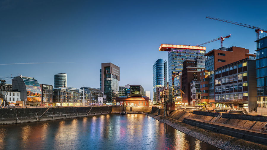 Illuminated buildings by river against blue sky