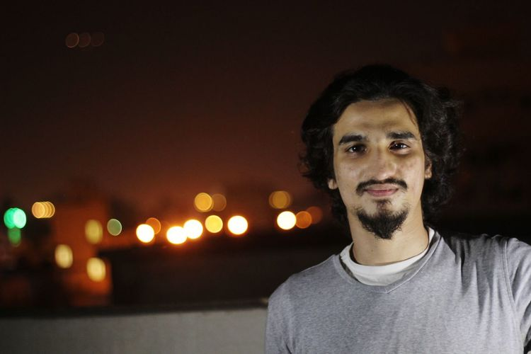 Portrait of man against illuminated lights at night