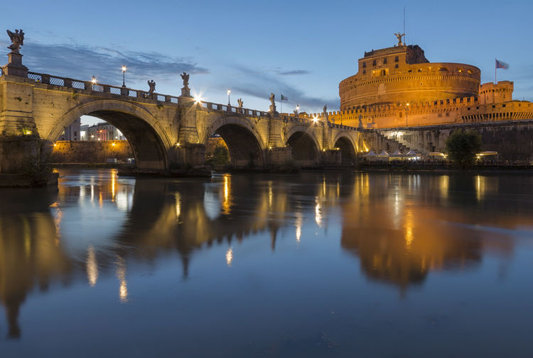 Ponte sant angelo over tiber river in city at dusk