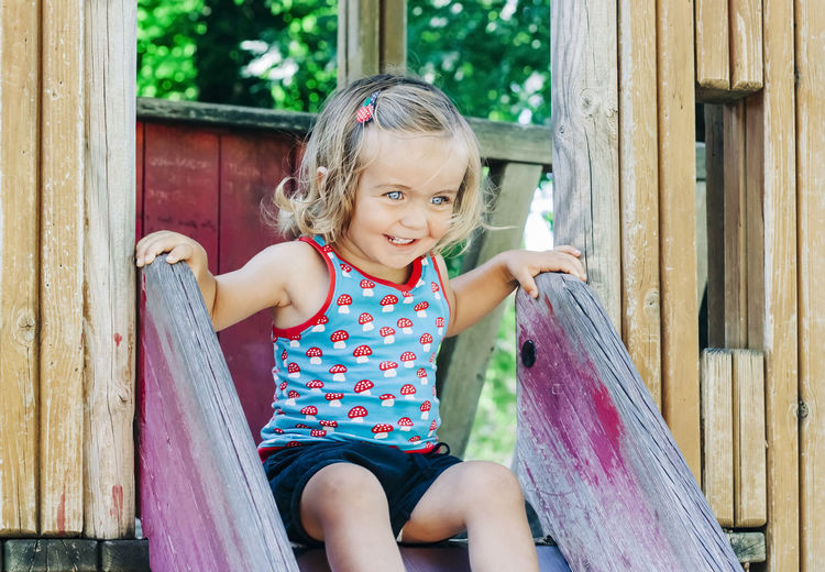 Smiling Girl Sitting On Slide At Playground