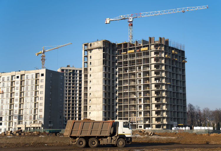 Construction site by buildings against clear blue sky