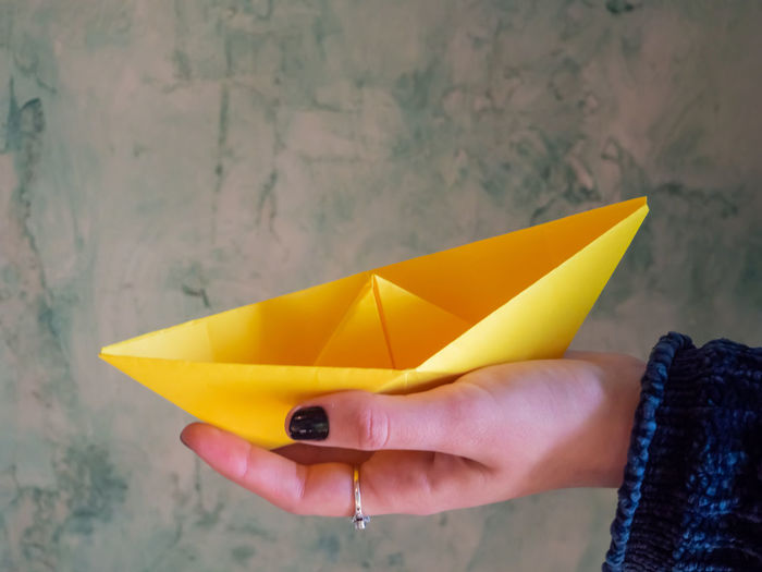 Cropped woman holding yellow paper boat