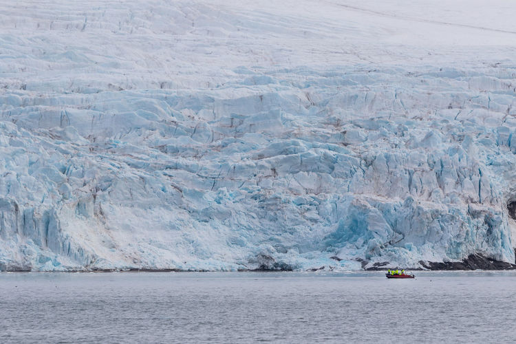 Unidentified tourists on a speedboat admiring large glacier from a close distance in svalbard