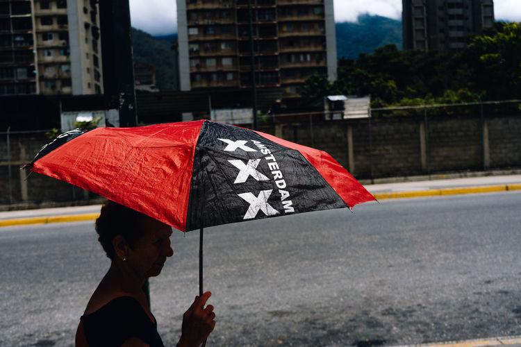 Man holding umbrella on street in rainy season