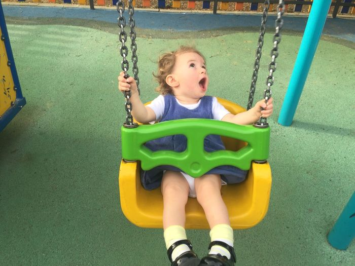 High Angle View Of Girl Swinging At Playground